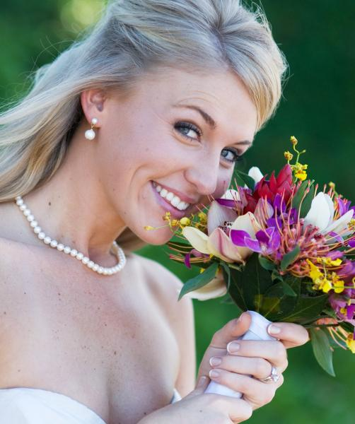 A wedding bouquet adds a pop of color when held against a traditional wedding dress.
