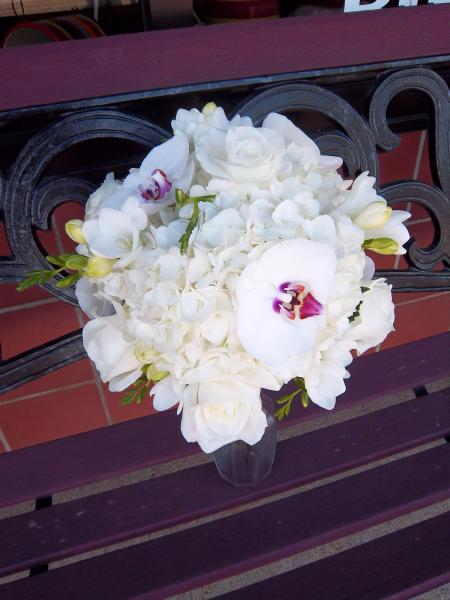 Phalaenopsis orchids, white roses, fragrant freesia and white hydrangea.