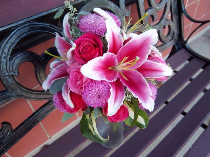 Locally grown hot pink dahlias, hot pink roses, stargazer lilies, accented with hosta leaves.