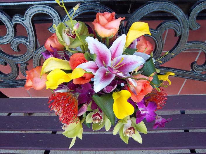 [Image: Gorgeous tropical bridal bouquet, orange pin cushion protea, stargazer lilies, yellow calla lilies, lime green dendrobium orchids, bright orange roses.]