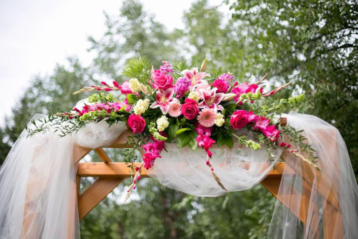 [Image: Pergola decorated at Courtyards of Andover, beautiful roses, gerbera daisies, gladiola and stock]