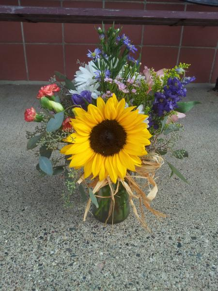 Designed with sunflowers, monte casino, orange mini carnations and a variety of other flowers, tied off with raffia.]