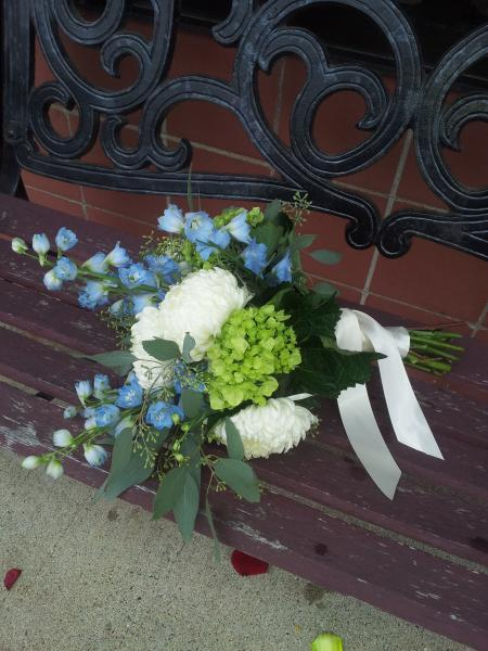 [Image: Light blue delphinium, white football mums, green hydrangea and seeded eucalyptus tied with a soft ivory satin ribbon.]