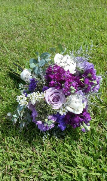 Shades of purple, roses, stock, trachillium, lisianthus, eucalyptus, statice and waxflower.