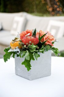 [Image: Rose roses, pin cushion protea designed in a concrete square contemporary vase.]