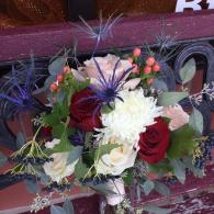 Thistle, viburnum berries, champagne, ivory and deep red roses, peach hypericum berries.