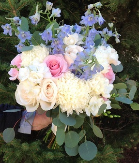 Light blue delphinium, standard mums, roses, freesia and seeded eucalyptus.