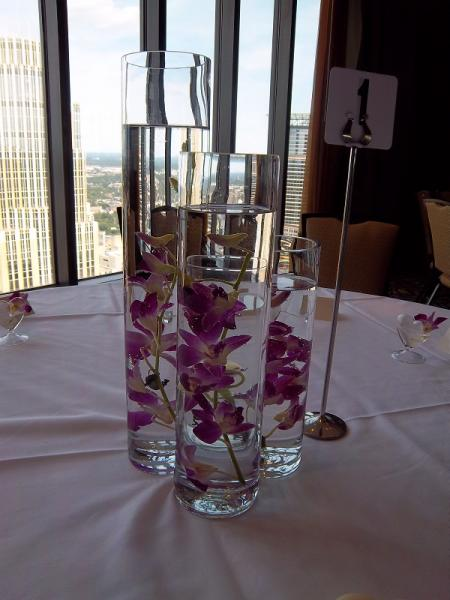 [Image:  This centerpiece can be designed with a variety of fresh flowers suspended in the water and accented with a floating candle.]