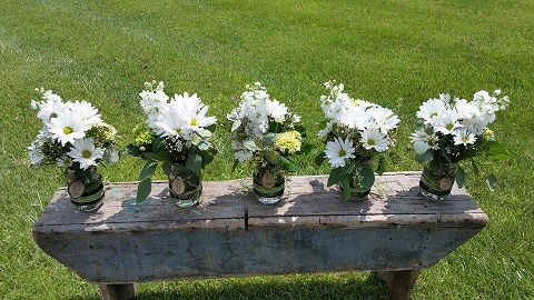 [Image:  These beautiful bouquets were designed in Mason Jars with monogrammed wooden circles.]