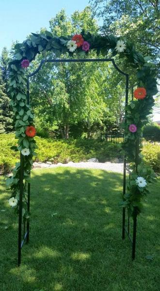 [Image: Arbor decorated with fresh mixed greenery and gerber daisies.]