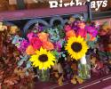 Large sunflowers with orange and pink roses, fragrant stock and eucalyptus.