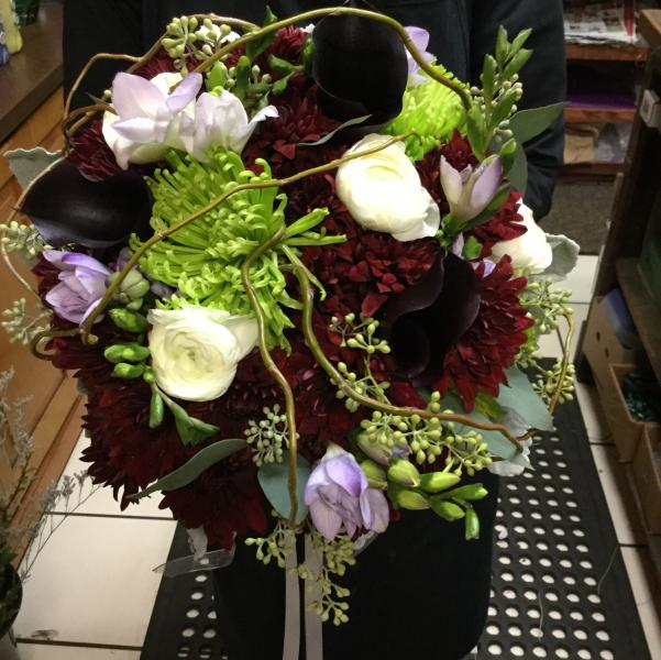 [Image: Burgundy dahlias, white ranunculus, lavender freesia, green spider mums, seeded eucalyptus all accented with curly willow.]