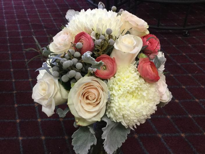 [Image: Soft white football mums, peach ranunculus, bruins berries, ivory roses accented with dusty miller.]