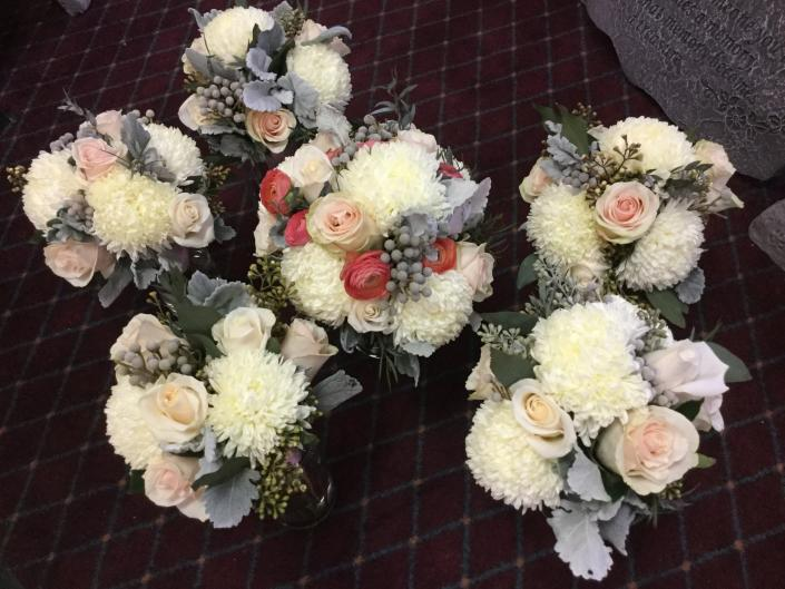 [Image: Ivory and blush roses, ranunculus, football mums, Bruneian berries and dusty miller.]