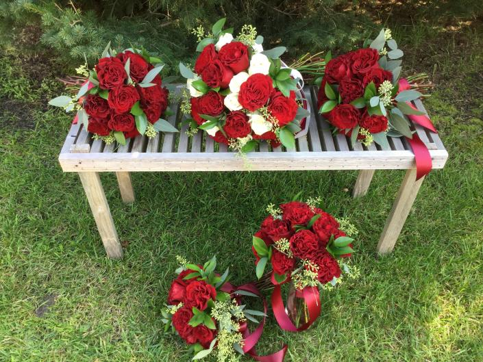 "Bride and bridesmaids bouquets, deep red ""heart"" roses, white roses and a variety of greenery."