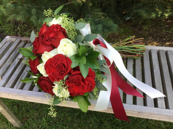 "[Image: Deep red ""heart"" roses designed with white roses, seeded eucalyptus and israeli ruscus.]"