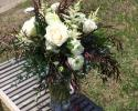 White roses and ranunculus, astilbe and a variety of eucalyptus.