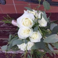 Large and mini fragrant white roses, a variety of eucalyptus and leatherleaf fern, tied off with champagne ribbon.