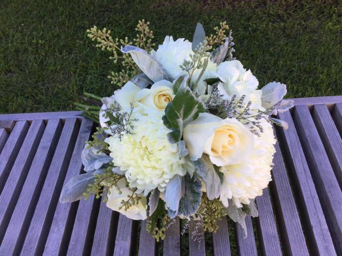[Image: Ivory roses, standard mums, seed eucalyptus, dusty miller.]