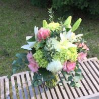 Lime green roses and mini hydrangea, white football mums and lilies, light pink alstromeria accented with eucalyptus.