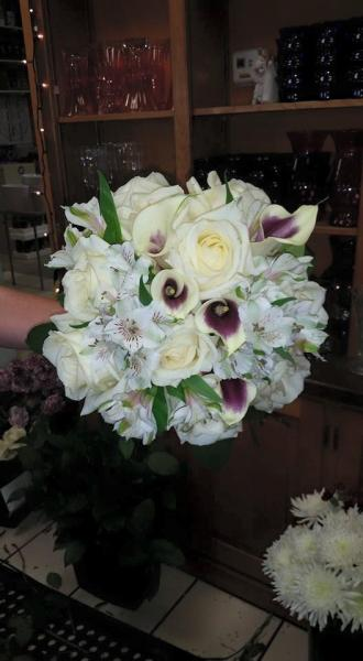 White calla lilies with purple inside, white alstromeria, roses.