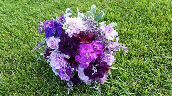 Shades of purple roses, stock and carnations. Bright blue delphinium, limonium and verigated pittsoporum.