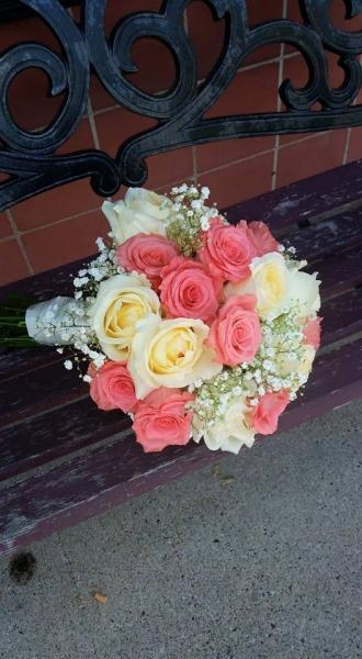 "Salmon colored ""movie star"" rose, pale yellow roses and babies breath."