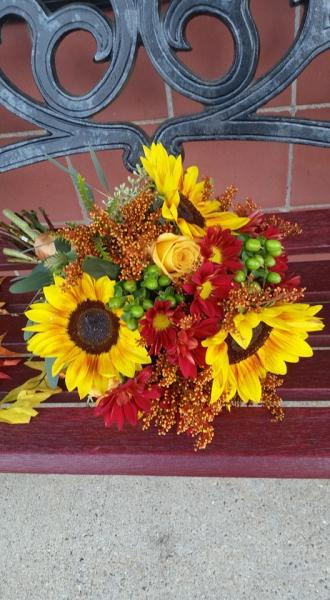 [Image:  Rust sunflowers, tinted solidago, fall mums and green hypericum berries.]