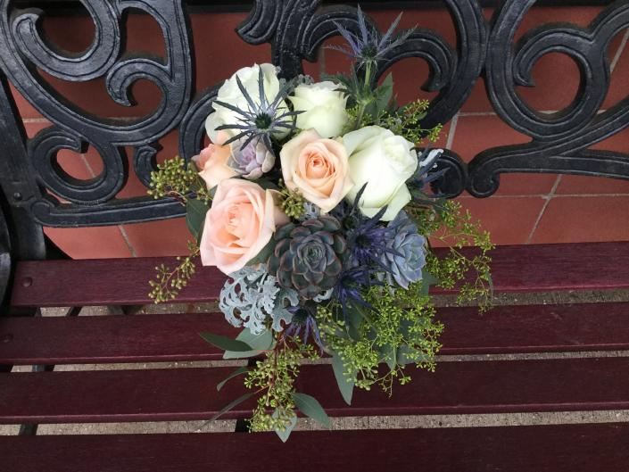 [Image: This bouquet designed with light peach and ivory roses, succulents, seeded eucalyptus, dusty miller and light blue thistle.]
