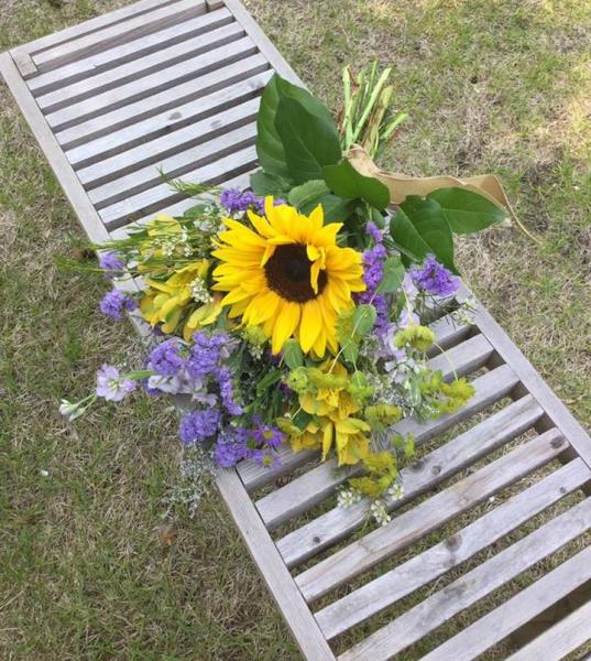 Yellow sunflowers, lavender statice and larkspur, yellow alstromeria, ladies mantle and white waxflower.