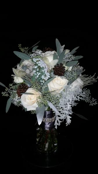 [Image: Ivory roses, berzillia berries, dusty miller, seeded eucalyptus (sprayed a hint of silver), minature pine cones tied off with satin pewter ribbon and a crystal wrap.]